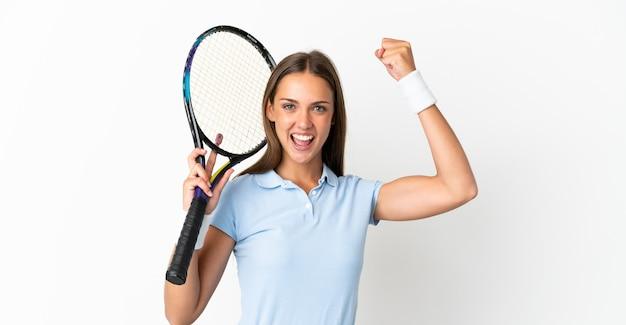 Jonge vrouw geïsoleerd tennissen en vieren van een overwinning