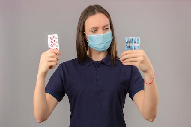 Jonge vrouw, gekleed in blauw poloshirt in medische masker verward kijken naar blister met pillen in handen en denken keuze maken staande op lichtgrijze achtergrond
