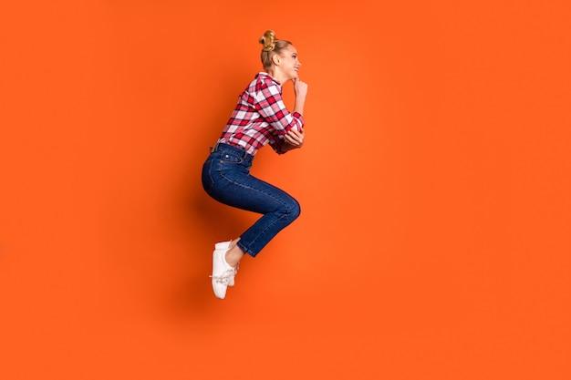 Jonge vrouw gekleed in een geruite geruit overhemd springen en poseren geïsoleerd op oranje