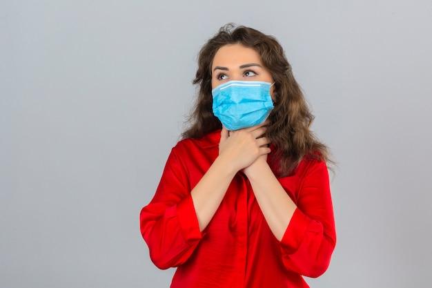 Jonge vrouw, gekleed in een rode blouse in medisch beschermend masker kijkt onwel haar nek aanraken en lijdt aan keelpijn over geïsoleerde witte achtergrond
