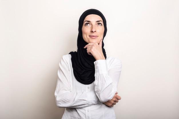 Jonge vrouw gekleed in een wit overhemd en hijab houdt haar hand tegen haar kin en kijkt met een peinzend gezicht op