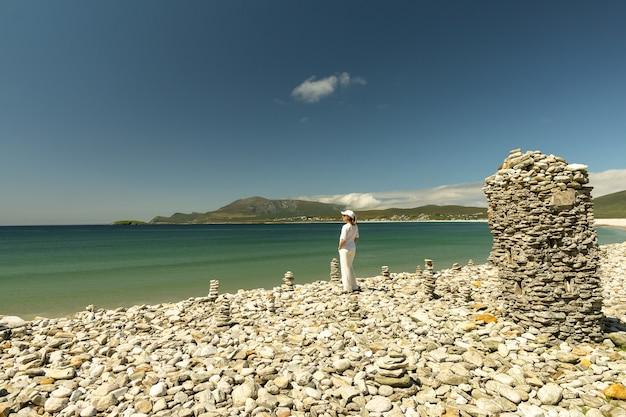 Jonge vrouw gekleed in het wit kijkend naar rotsachtig strand bij keel beach achill island ireland
