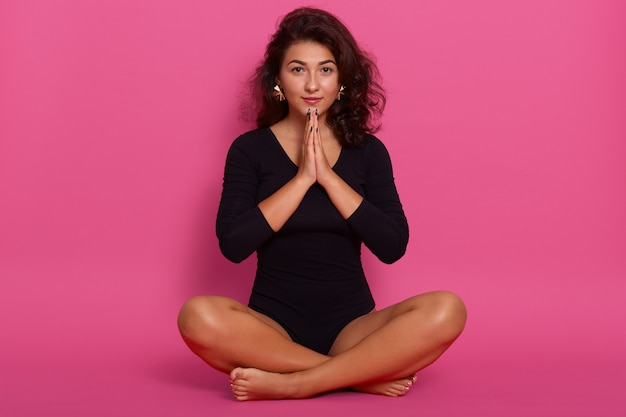 Jonge vrouw, gekleed in kombidress, zittend op de vloer in lotus houding, schattig meisje hand in hand in gebed gebaar, brunette vrouwelijke poseren geïsoleerd op roze.