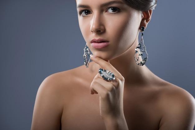 Jonge vrouw, gekleed in prachtige zilveren sieraden met blauwe en witte edelstenen op zoek vol vertrouwen op grijs