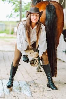 Jonge vrouw gekleed in rijkleding die de hoeven van haar bruine paard in een stal schoonmaakt.