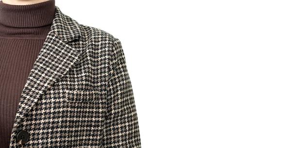 Jonge vrouw, gekleed in stijlvol bruin tweed houndstooth patroon jasje of blazer close-up.