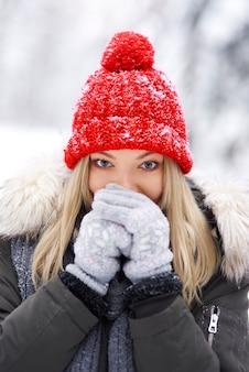 Jonge vrouw, gekleed in warme kleren rillen
