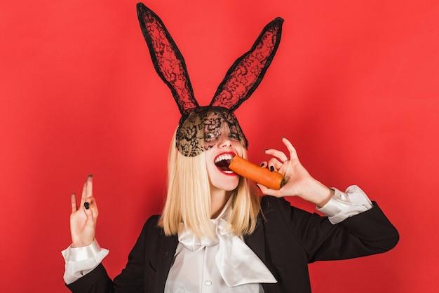 Jonge vrouw, gekleed in zwart kant pasen konijn oren met een wortel