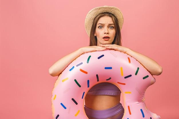 Jonge vrouw gekleed in zwembroek springen en houden zwemmen opblaasbare ring