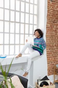 Jonge vrouw gekleed terloops bezig met laptop zittend op de vensterbank thuis. werk vanuit huis concept.