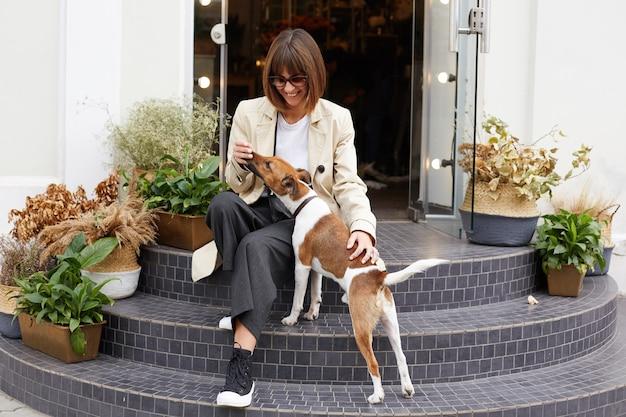 Jonge vrouw gekleed terloops zittend op café trappen glimlachen, spelen met haar mooie hond jack russell terrier