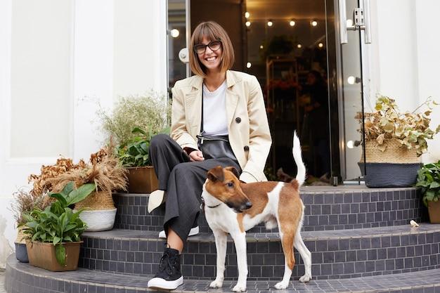 Jonge vrouw gekleed terloops zittend op trappen van bloemenwinkel lachend met haar mooie hond jack russell terriër