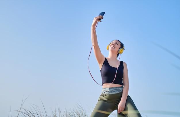Jonge vrouw gekleed voor sport die een selfie neemt