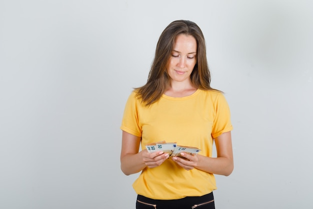 Jonge vrouw geld tellen in geel t-shirt, zwarte broek en voorzichtig kijken