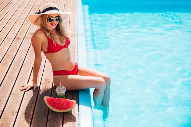 Jonge vrouw gelukkig aan de rand van het zwembad