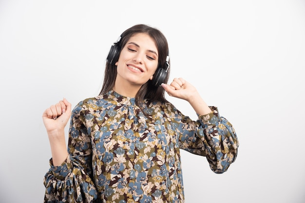 Jonge vrouw gelukkig dansen en muziek luisteren in de koptelefoon.