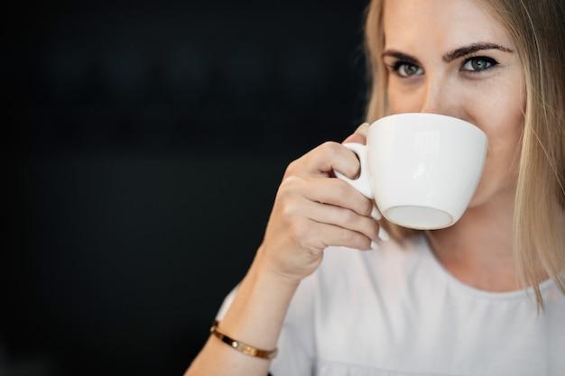 Jonge vrouw gelukkig drinken groene thee in een café