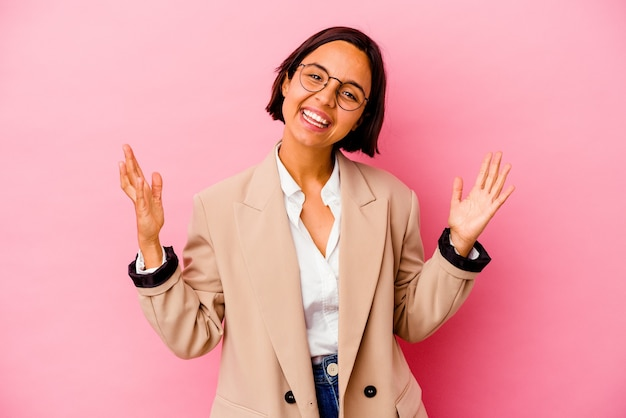 Jonge vrouw gemengd ras bedrijf geïsoleerd op roze achtergrond een overwinning of succes vieren, hij is verrast en geschokt.