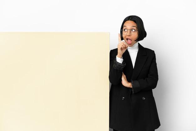 Jonge vrouw gemengd ras bedrijf met met een grote banner over geïsoleerde achtergrond van plan om de oplossing te realiseren terwijl het opheffen van een vinger