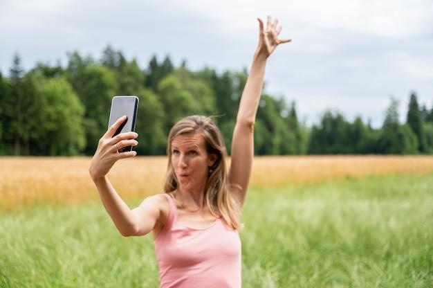 Jonge vrouw geniet van de natuur en maakt selfies terwijl ze haar arm opheft en een grappig gezicht maakt. met focus op de mobiele telefoon.