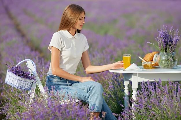 Jonge vrouw geniet van diner in lavendelveld