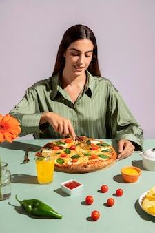 Jonge vrouw geniet van een heerlijke pizza Gratis Foto