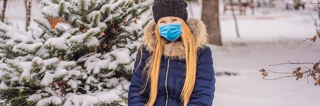 Jonge vrouw geniet van een winterse besneeuwde dag in een besneeuwd bos met een medisch masker tijdens covid-19