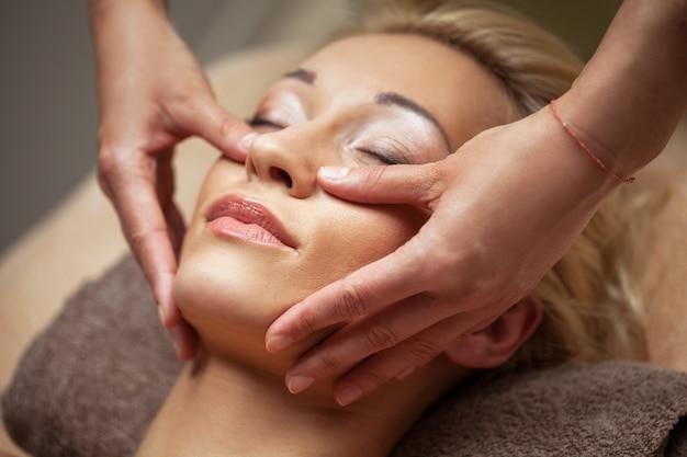Jonge vrouw geniet van gezichtsmassage in kuuroord