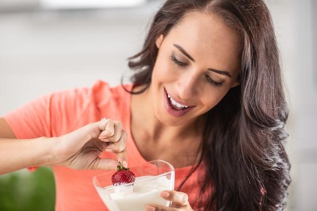 Jonge vrouw geniet van het onderdompelen van verse aardbeien in een kom slagroom.