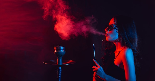 Jonge vrouw geniet van het roken van een waterpijp