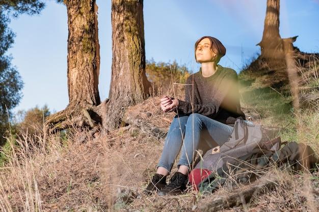 Jonge vrouw geniet van mooi herfstweer. vrouwelijke wandelaar zit onder pijnbomen op een zonnige middag