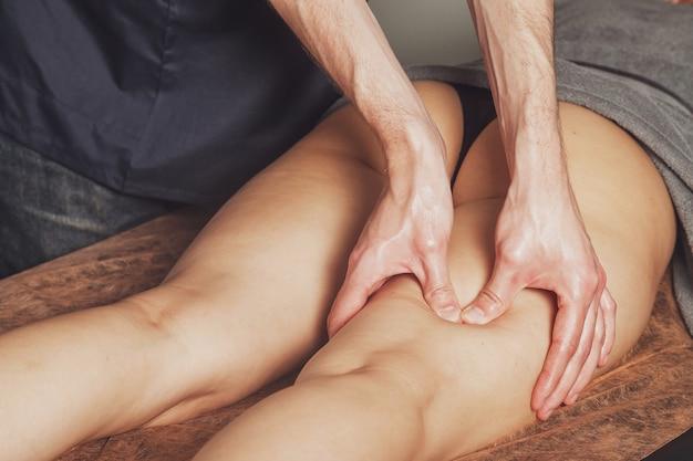 Jonge vrouw geniet van sport wellness-massage in het medische kantoor van de fitnessruimte. professionele thuismassagetherapeut doet massageoefeningen. concept van ontspanning, schoonheid, gezondheid, lichaamsverzorging. ruimte kopiëren