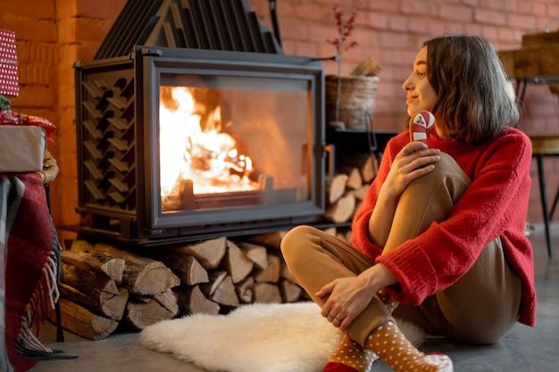 Jonge vrouw geniet van vuur terwijl ze tijdens de wintervakantie met kerstsnoep bij de open haard zit. warmte en gezelligheid in winterconcept