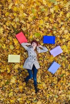 Jonge vrouw geniet van winkelen in herfst park. veelkleurige boodschappentassen. verticaal kader.