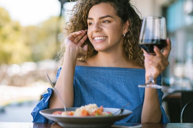 Jonge vrouw genieten en ontspannen tijdens de lunch in een restaurant.