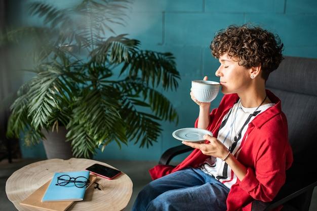 Jonge vrouw genieten van aromatische koffie of thee terwijl ze het ruikt voordat ze tijdens pauze in café proeft