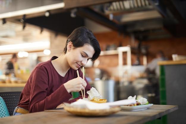 Jonge vrouw genieten van aziatisch eten in cafe