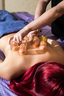 Jonge vrouw genieten van cupping rugmassage in de spa. de handen van de mannelijke arts zetten vacuüm plastic blikjes. ontspanning, schoonheid, lichaamsbehandeling concept. thuismassage.