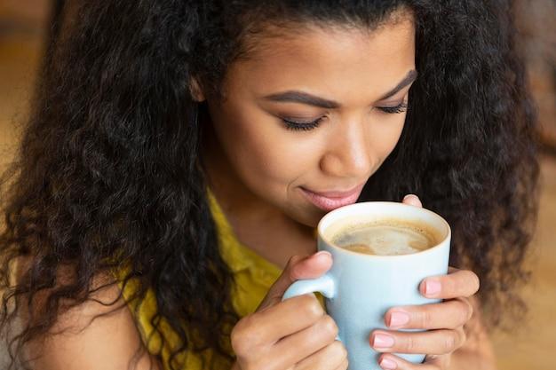 Jonge vrouw genieten van een kopje koffie