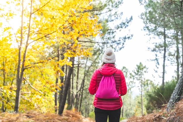 Jonge vrouw genieten van herfst buiten. meisje wandelen in de berg.