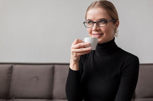 Jonge vrouw genieten van koffie