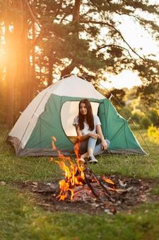 Jonge vrouw genieten van vreugdevuur buitenshuis