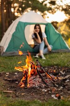 Jonge vrouw genieten van vreugdevuur in de natuur