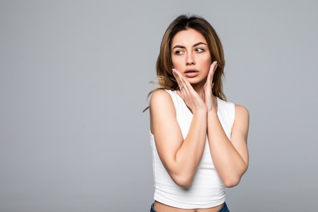 Jonge vrouw geschokt door het slechte nieuws, geïsoleerd op een grijze muur