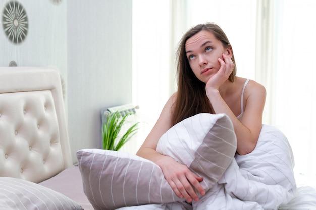 Jonge vrouw gestoord door luidruchtige buren terwijl ze probeert in slaap te vallen in bed thuis