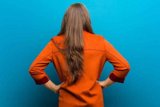 Jonge vrouw gevoel verward of vol of twijfels en vragen, benieuwd, met de handen op de heupen, achteraanzicht tegen blauwe muur