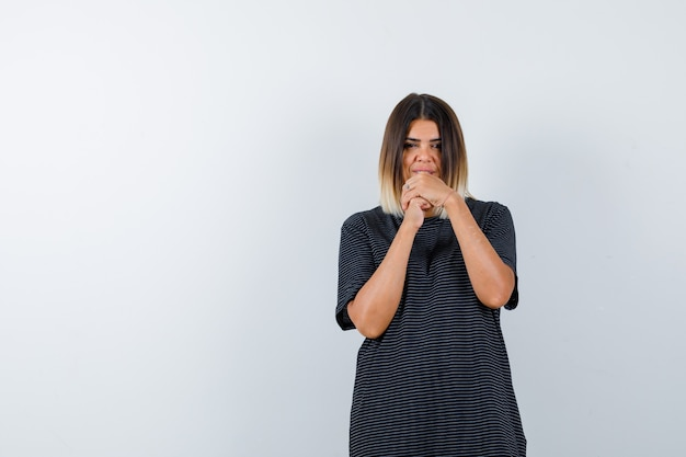 Jonge vrouw gevouwen handen in de buurt van gezicht in polokleding en hoopvol kijkt. vooraanzicht.