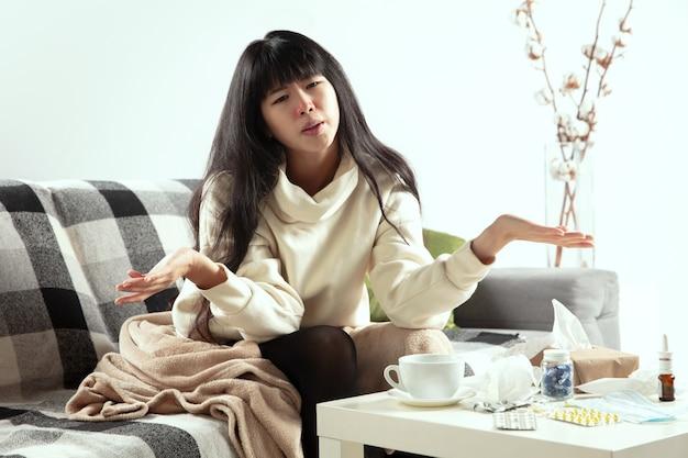 Jonge vrouw gewikkeld in plaid ziet er ziek uit, niest en hoest thuis op de bank