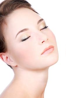 Jonge vrouw gezicht close-up met gesloten ogen, ontspanning concept.