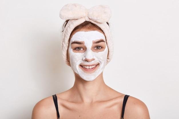 Jonge vrouw gezicht crème aanbrengend terwijl poseren geïsoleerd op witte achtergrond, dame jurken haarband met strik, glimlachend camera kijken, huidverzorging procedures doen.